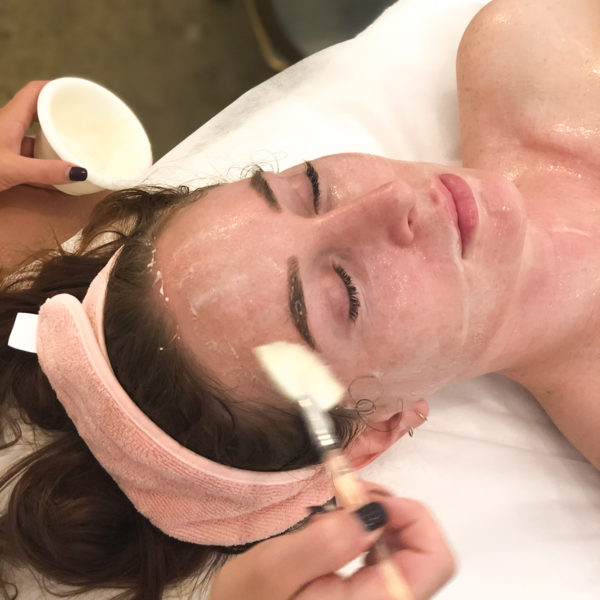 A lady getting her face cleansed with product - QLD, NSW